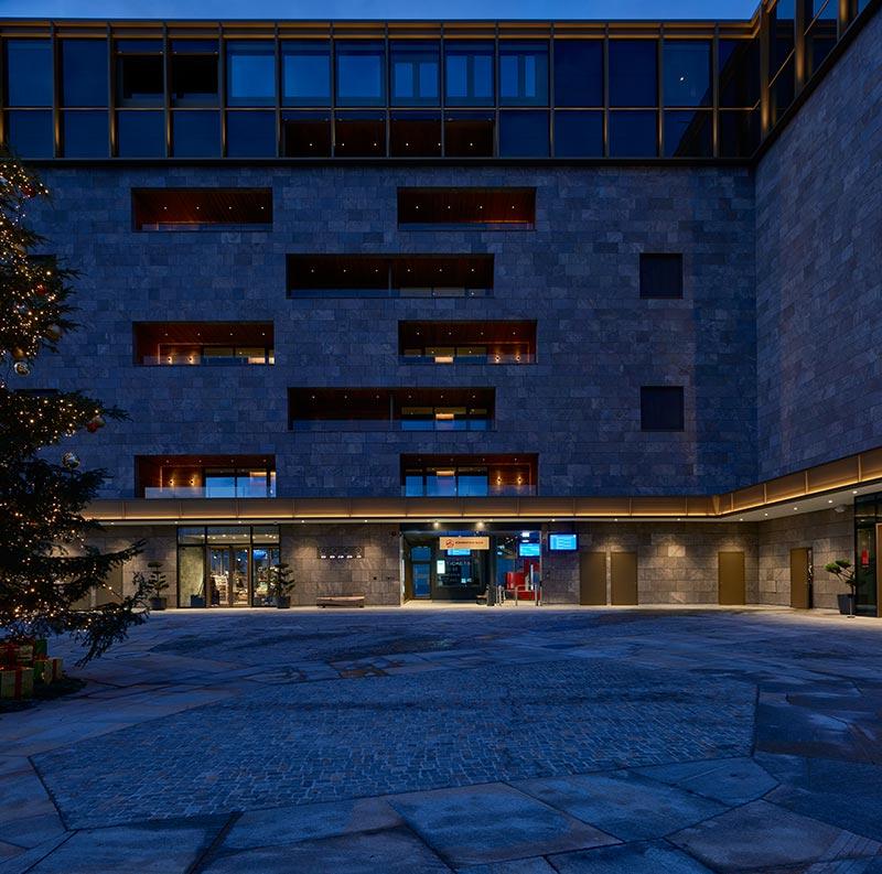 An der Südfassade bilden die zwei Gebäudeflügel des Bürgenstock Hotels eine Piazza aus. Veranstaltungen und Open-Air-Kinovorstellungen können die Gäste von den in die Fassade integrierten Vip-Lounges aus betrachten. Das Licht ist daher stark gedämpft und blendungsreduziert.
