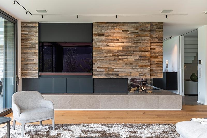 Justierbare Spy-Strahler von Delta Light leuchten die Wohnraumwand aus edlem Altholz aus und heben deren Farben und Plastizität hervor.
