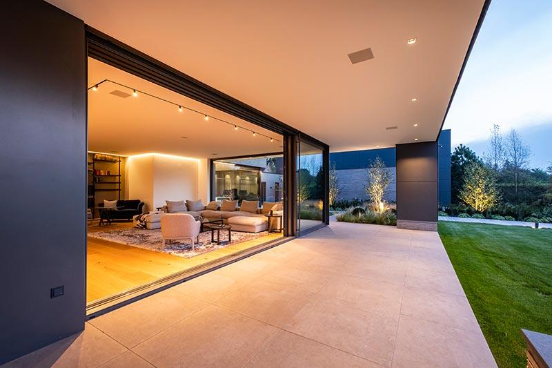 Die im Innenraum verlegten großformatigen Feinsteinzeugfliesen in Beton-Optik setzen sich im Außenraum fort. Die Übergänge erscheinen fließend. Die dimmbaren Spy-Strahler in dem Leuchtenprofil tauchen den Wohnraum in ein schönes warmes Licht.