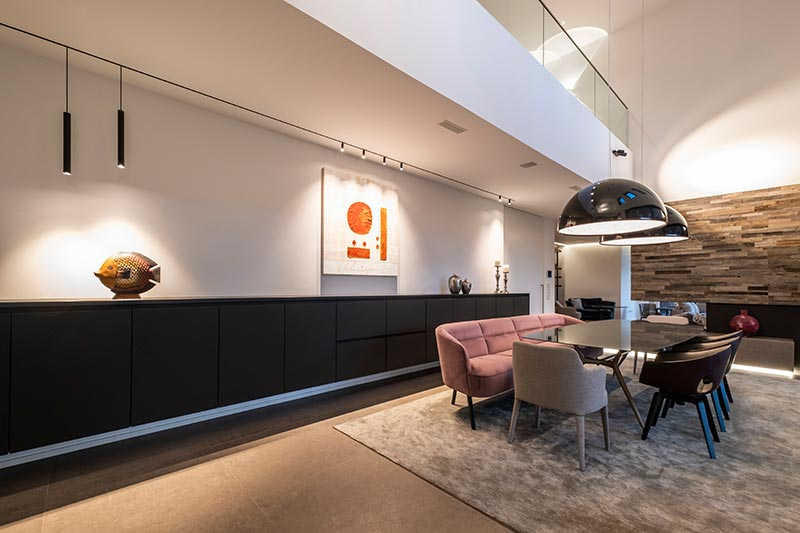 Wie im Wohnraum und in der Küche folgt auch im Essbereich ein magnetsiches Leuchtenprofil von Delta Light dem linearen Architekturkonzept. Tiefstrahlende Pendelleuchten ergänzen die justierbaren Spy-Strahler.