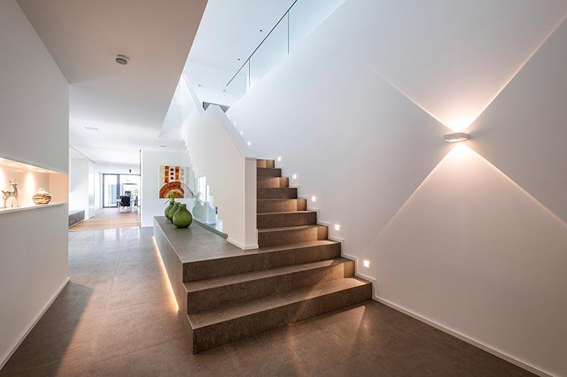 Der im rückwärtigen Gebäudeteil linear angelegte Flur wird durch Vision-Wandleuchten von Delta Light erhellt, welche die Wände spannend mit ihrer parabolischen Lichtverteilung dekorieren.