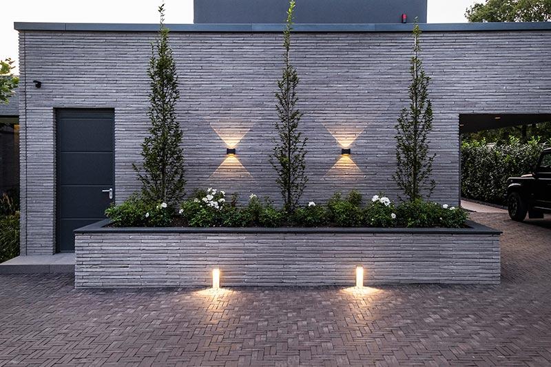 Die Beleuchtung der Außenanlagen erfolgt großteils mit Pollerleuchten von Delta Light. Elbo-Leuchten lassen die Riemchenkeramik des Bodenbelags zart schimmern. Vision-Wandleuchten erhellen die Fassaden mit zauberhaften Licht-Grafiken.